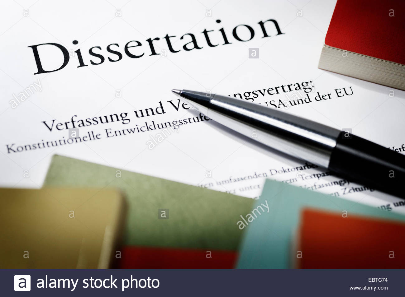 dissertation with books and pen, symbol picture 'plagiarism' - Stock Image