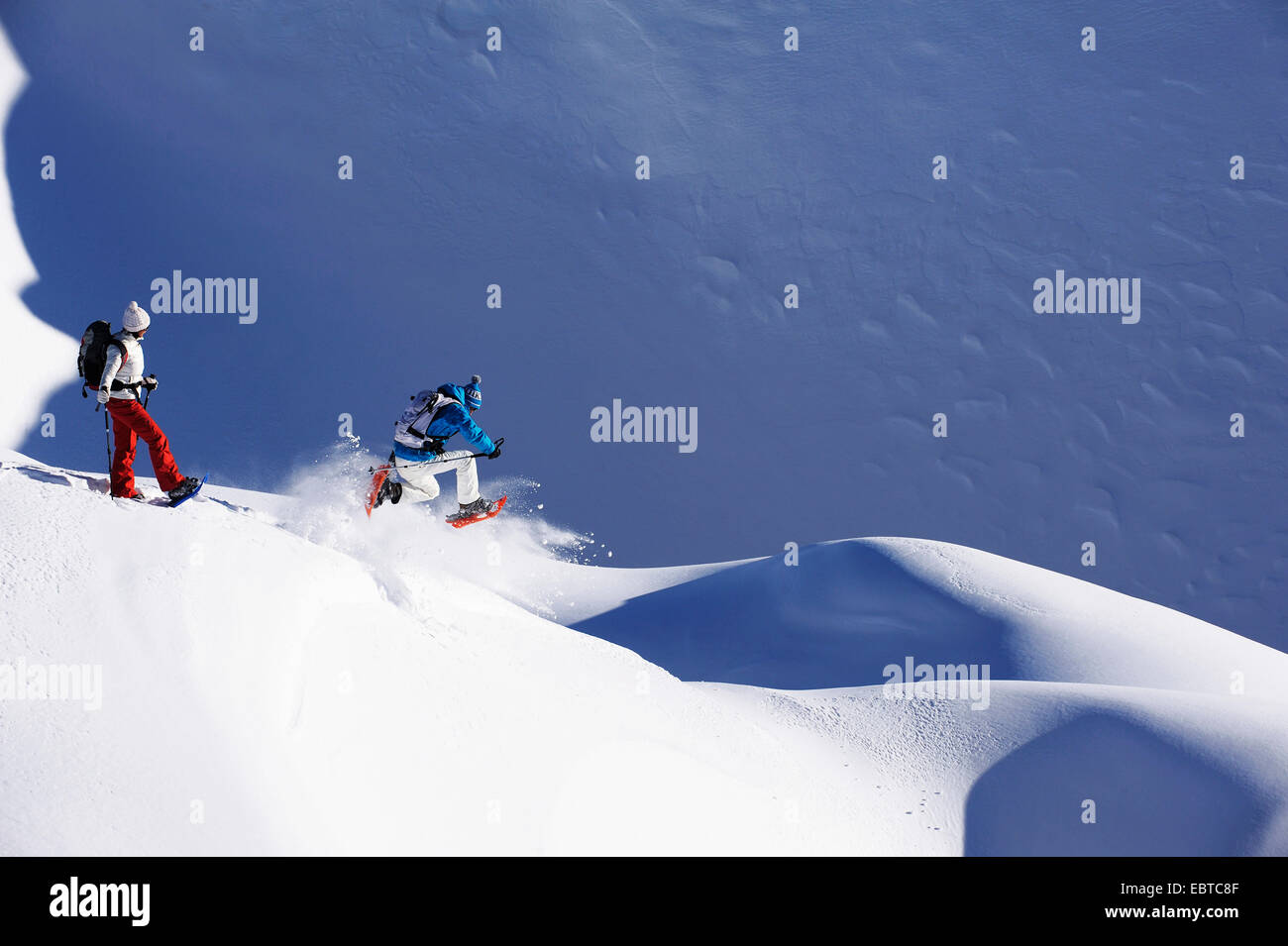 man and woman with snow shoes on a snow-covered slope, France Stock Photo
