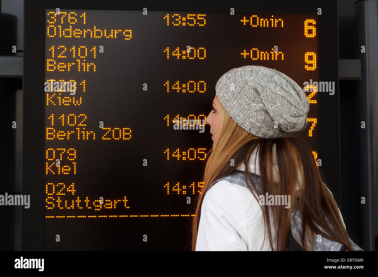 woman in front of destination board display at intercity bus station in germany - Stock Image