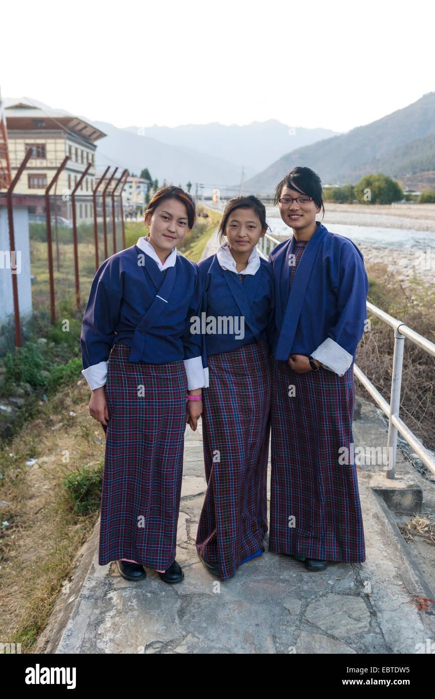 Three secondary school students in uniform at the Paro river bank, Bhutan - Stock Image