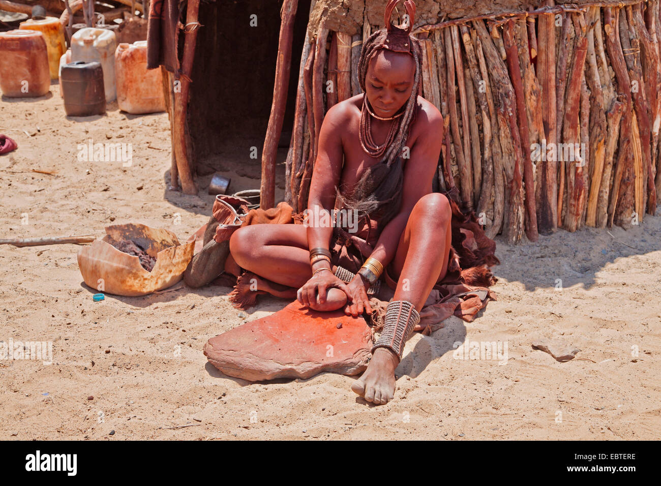 himba woman sitting in front of her hut and grinding up ocher, Namibia - Stock Image