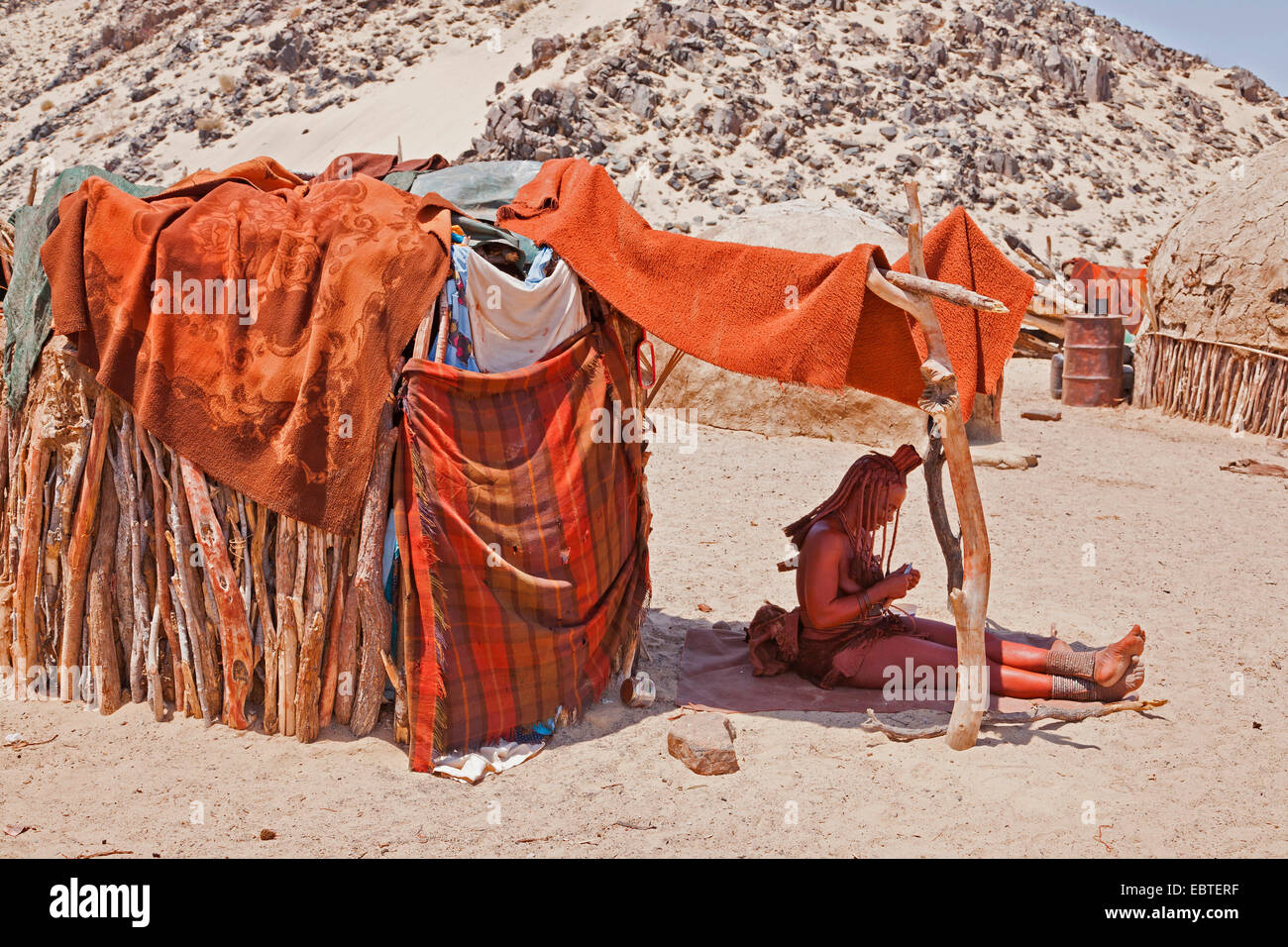 himba woman resting in the shade of her hut, Namibia - Stock Image