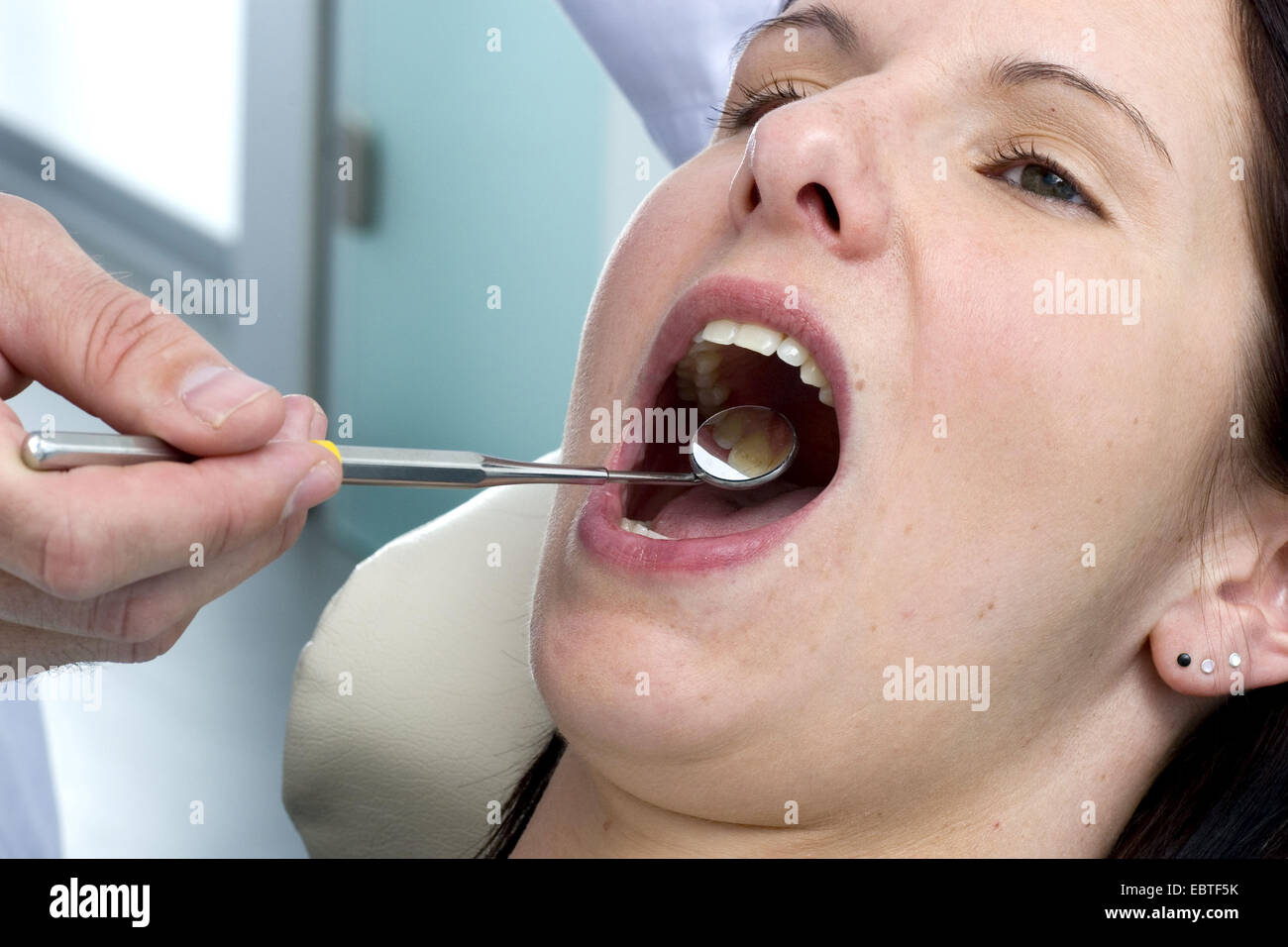 dentist checking teeth of a female patient - Stock Image