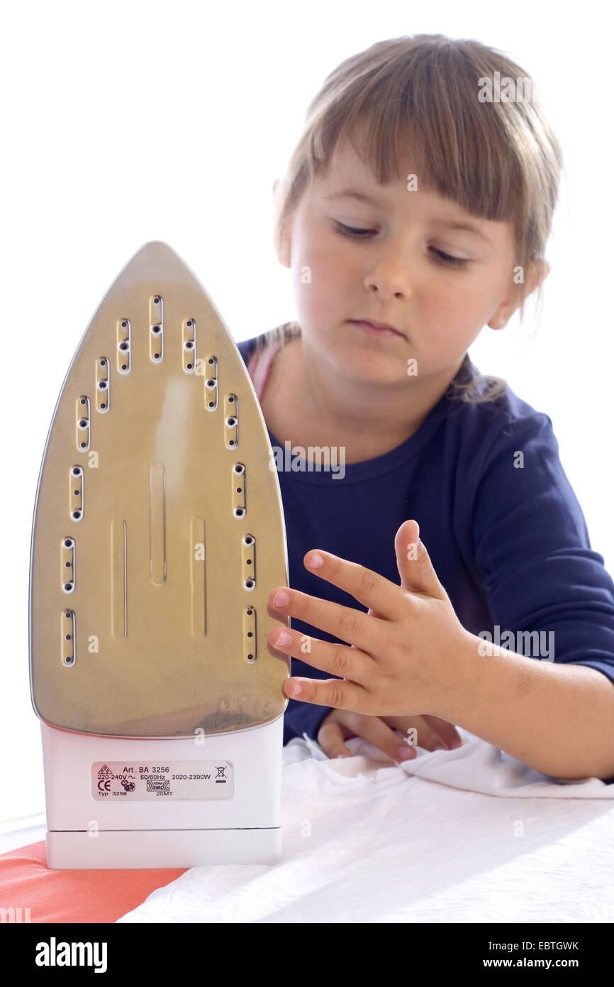 little girl touching carelessness a flat iron - Stock Image