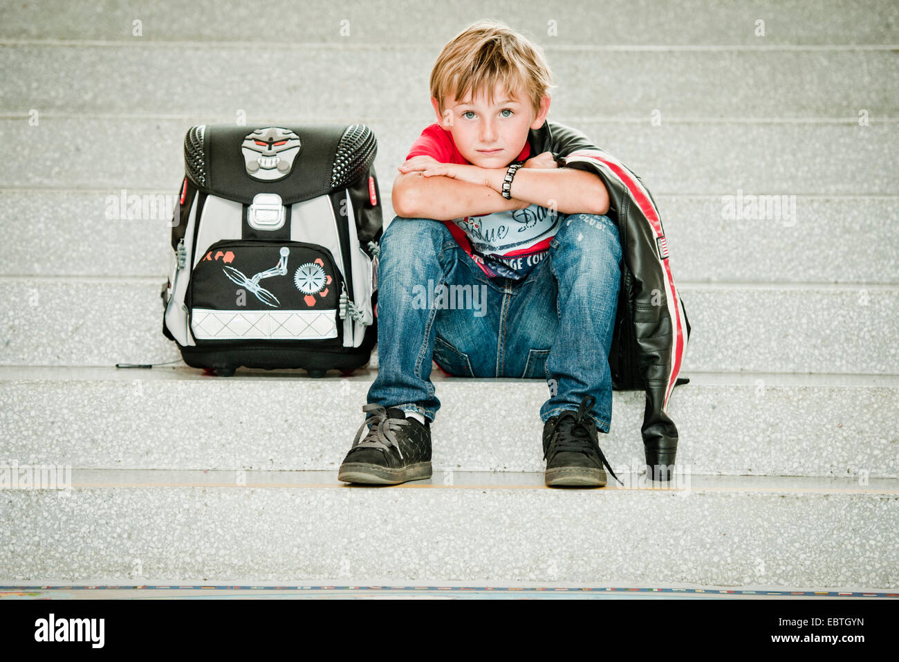 pupil with satchel sitting on stairs - Stock Image