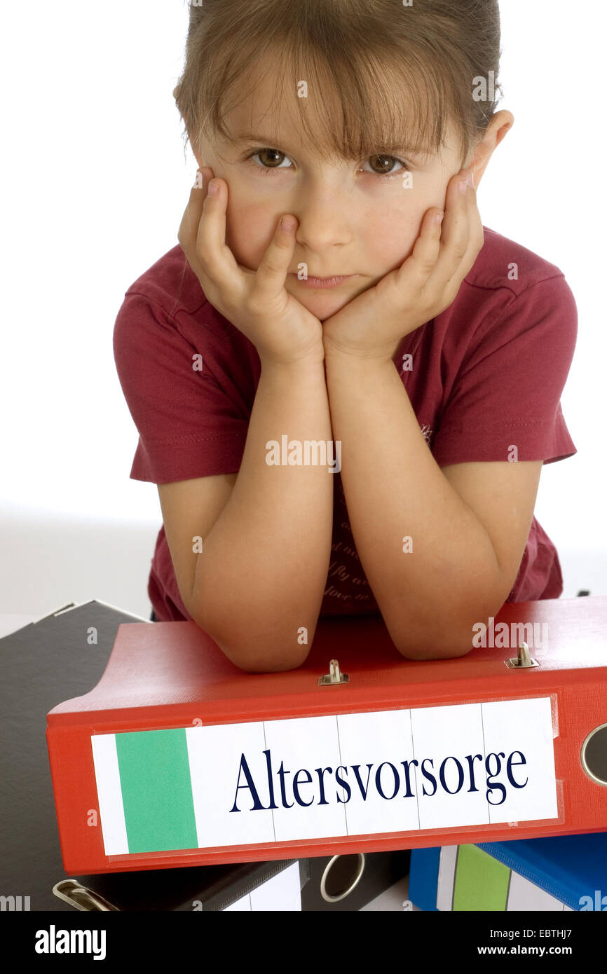 little girl seriously leaning on a file with the inscription 'Altersvorsorge' ('retirement planning') - Stock Image