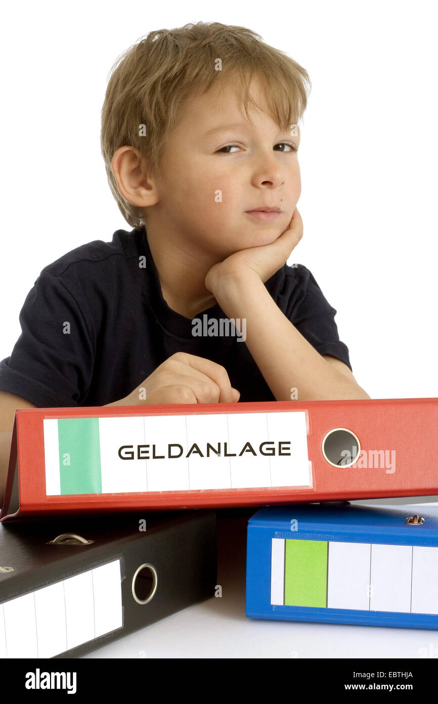 little boy seriously leaning on a file with the inscription 'Geldanlage' ('investment') - Stock Image