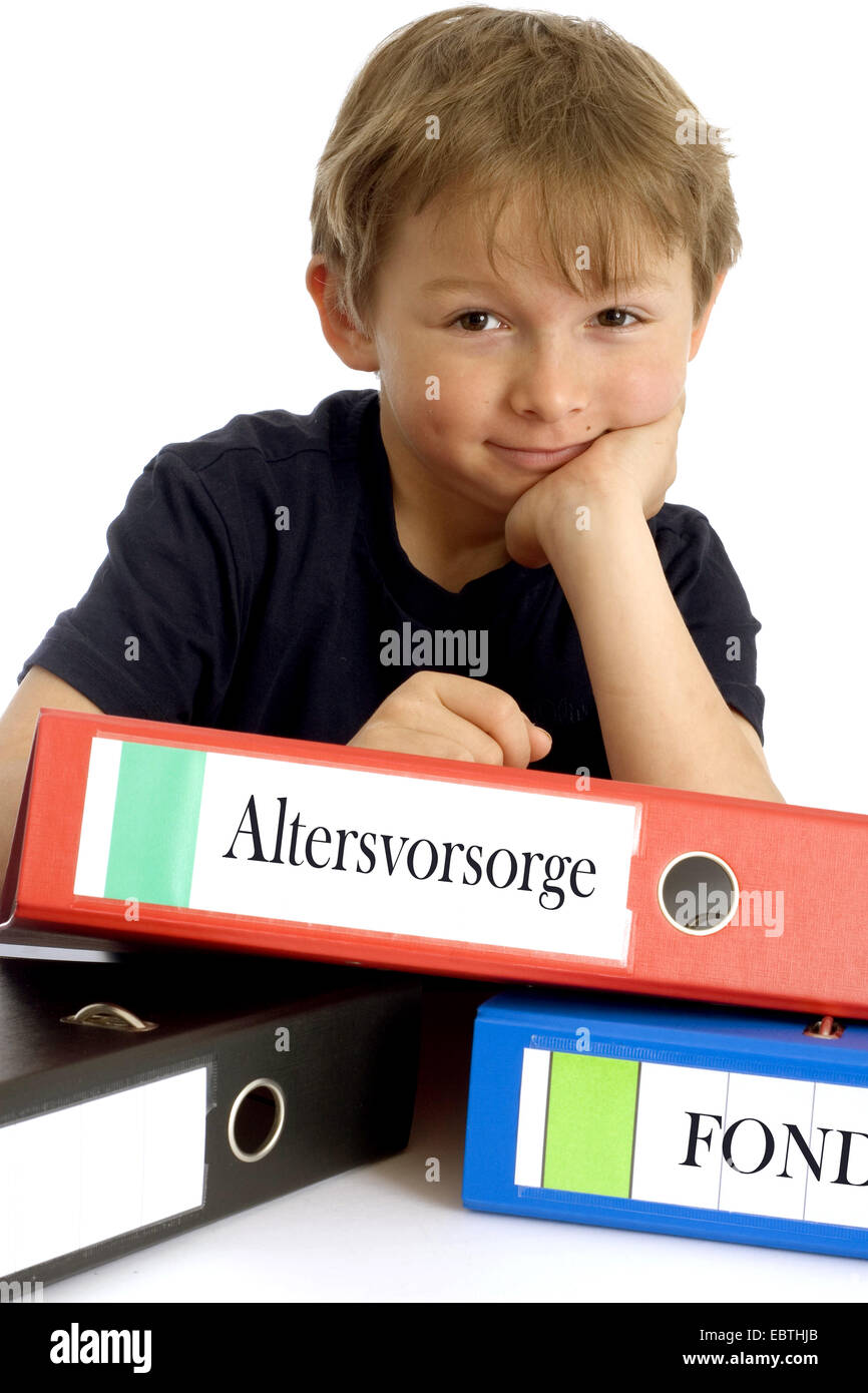 little boy smirking while leaning on a file with the inscription 'Altersvorsorge' ('retirement planning') Stock Photo