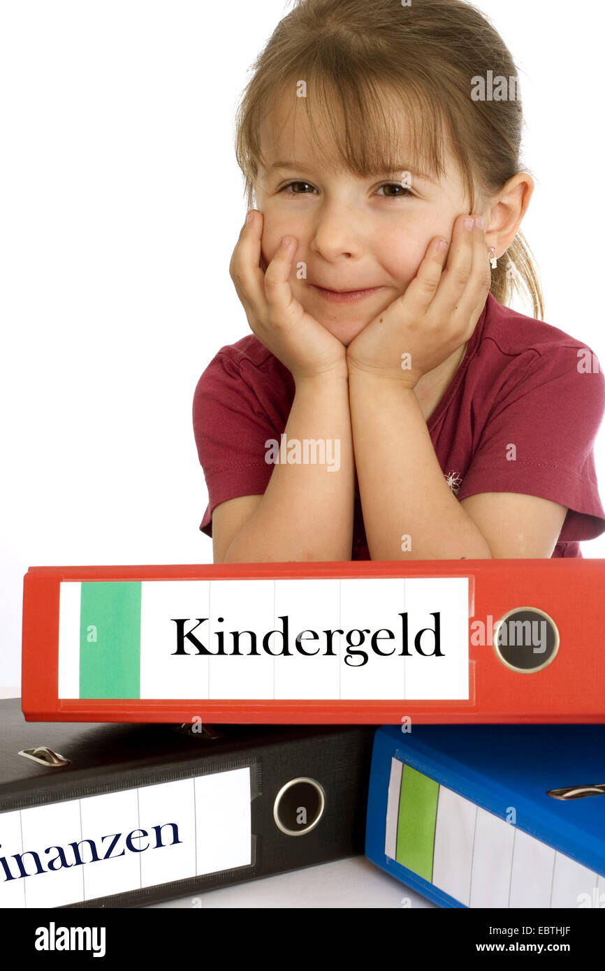 little girl smiling while leaning on a file with the inscription 'Kindergeld' ('child benefit') - Stock Image