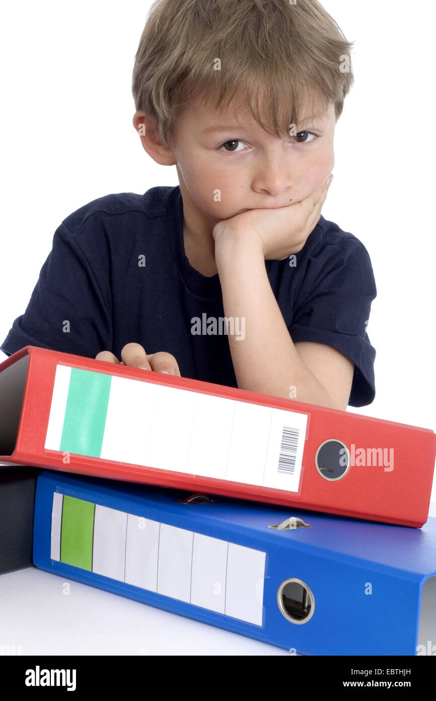 little boy leaning on a stack of files with a smile - Stock Image