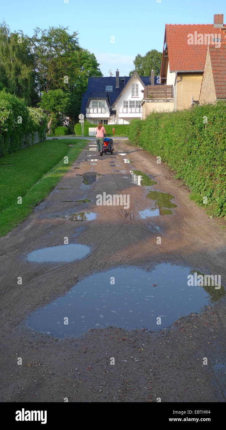 woman walking with buggy on a path with puddles, Germany - Stock Image