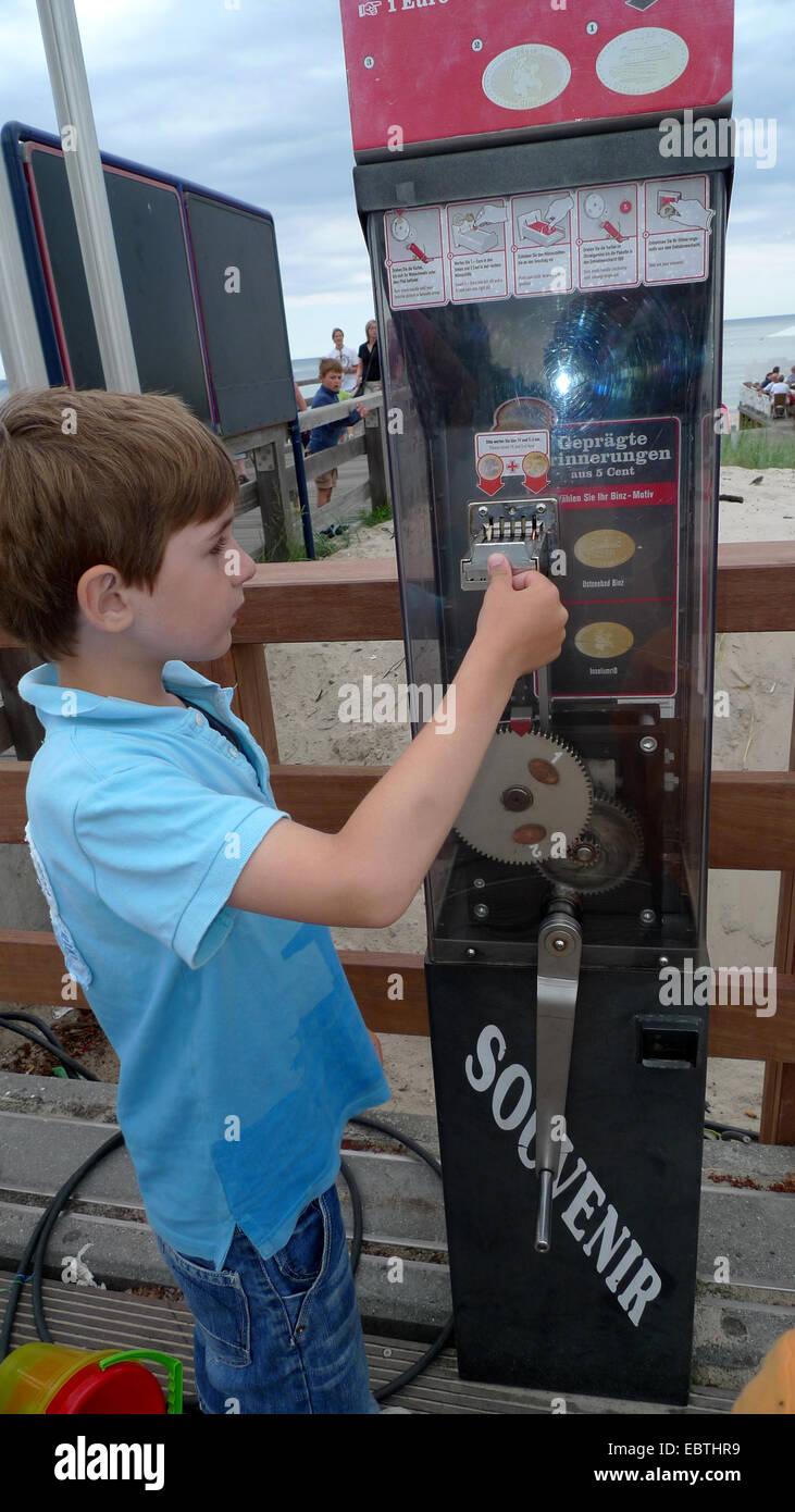 little boy at coin elongating machine, Germany, Mecklenburg-Western Pomerania, Ruegen - Stock Image