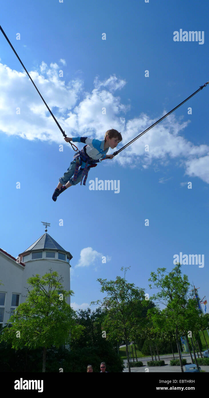 little boy jumping on bungee trampoline Stock Photo