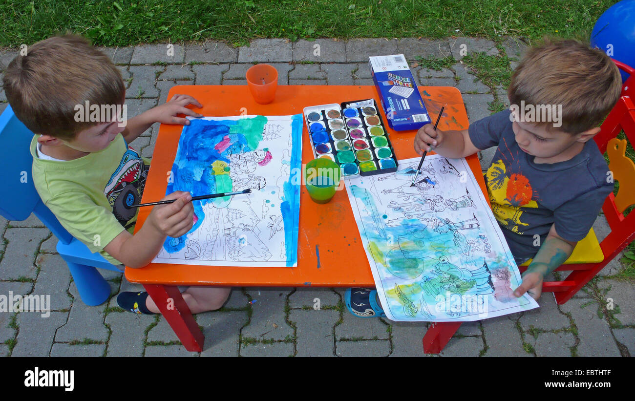 two children sitting in garden an painting with water colours Stock Photo