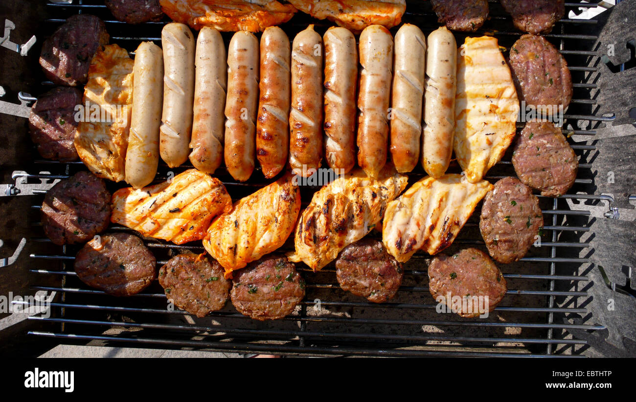 barbecue fare and sausages under the grill - Stock Image