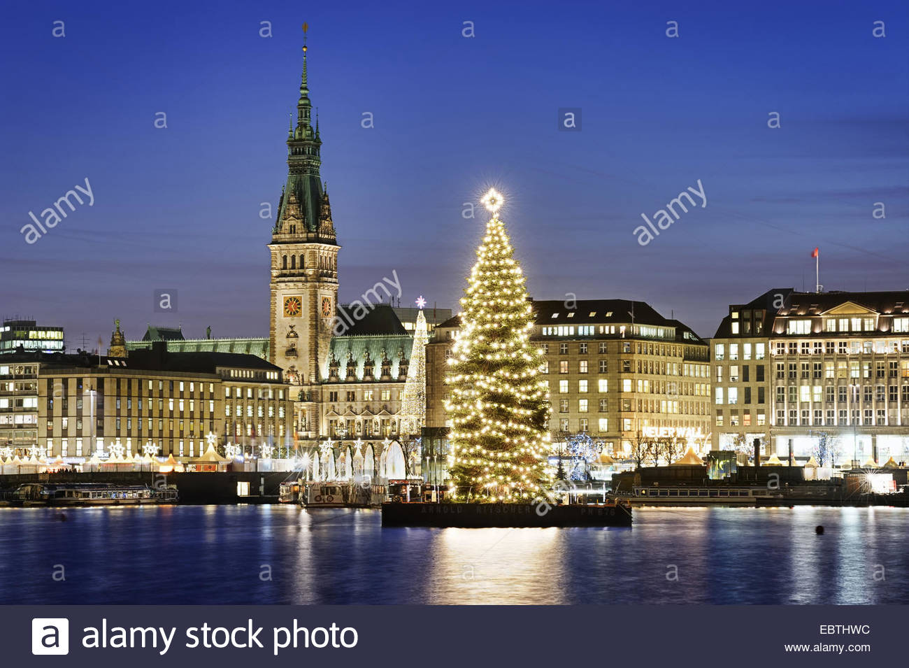 view over the Inner Alster Lake at the city centre in Christmas illumination with the town hall and a big Christmas - Stock Image