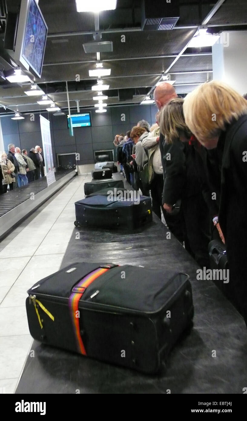 people waiting at a baggage reclaim at an airport - Stock Image