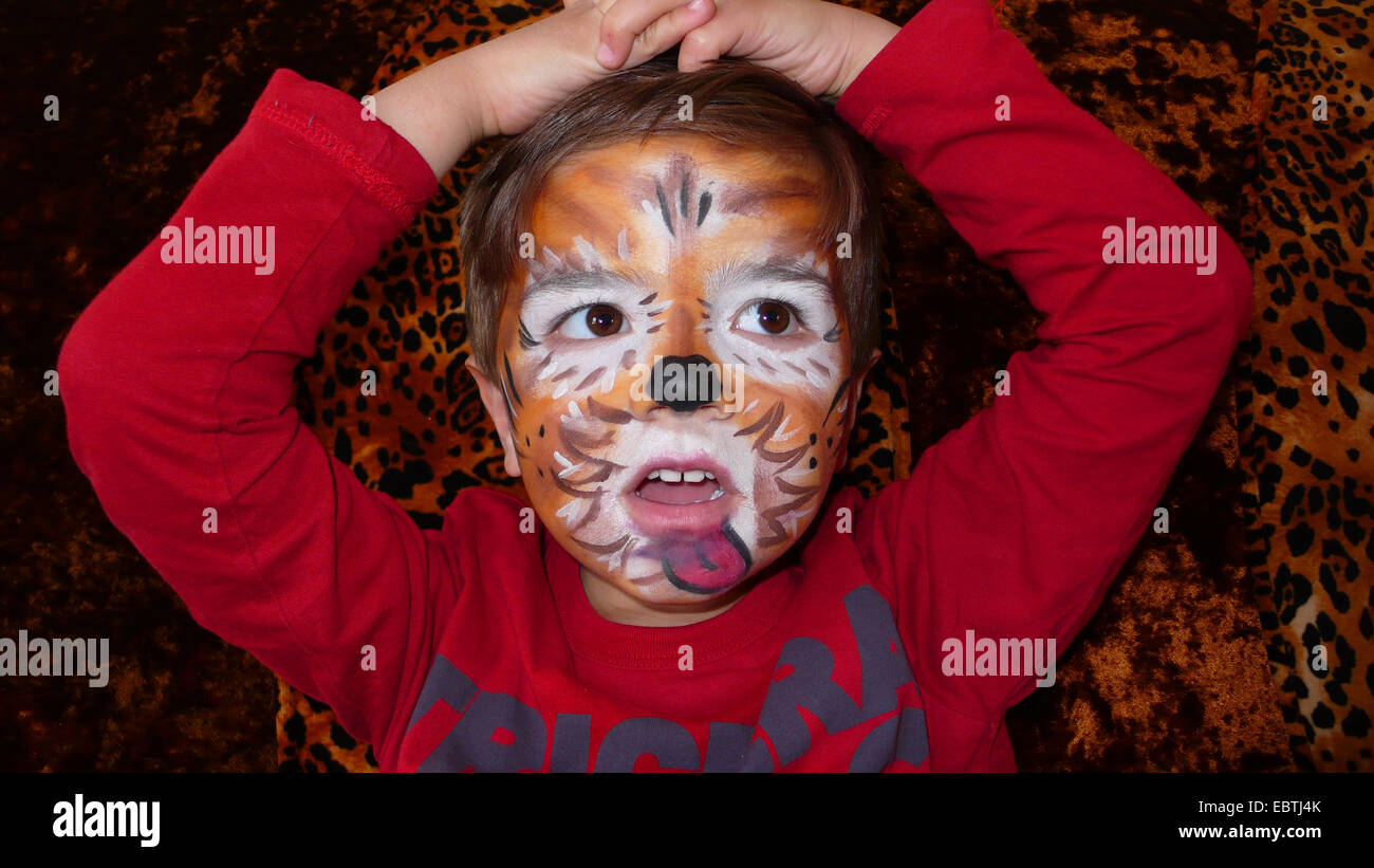 portrait of a little boy made-up as a tiger - Stock Image