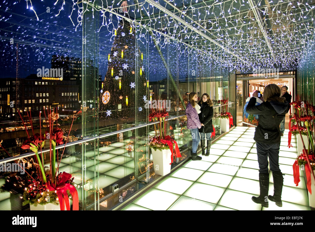 mother taking pictures of her two daughters in illuminated glass passage near Christmas market, Germany, North Rhine Stock Photo