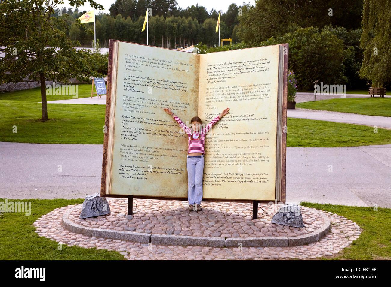 girl in an oversized book in Astrid Lindgren Vaerld, Astrid Lindgren World, Sweden, Smaland, Vimmerby - Stock Image