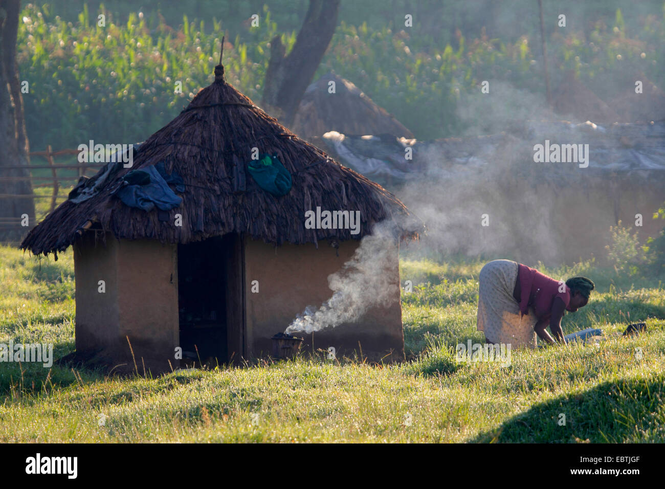 african woman working in front of her mud house, Uganda, Kisoro - Stock Image