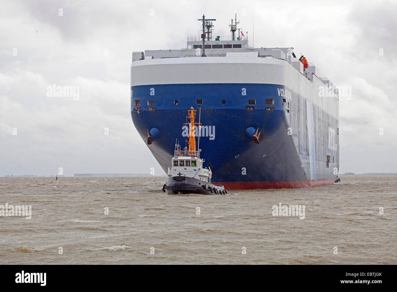 car carrier Voland Leader with towboat, Germany, Lower Saxony, East Frisia, Emden - Stock Image
