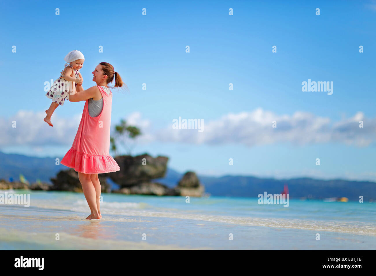 young mother playing with der daughter on the sandy beach, Philippines, Boracay - Stock Image