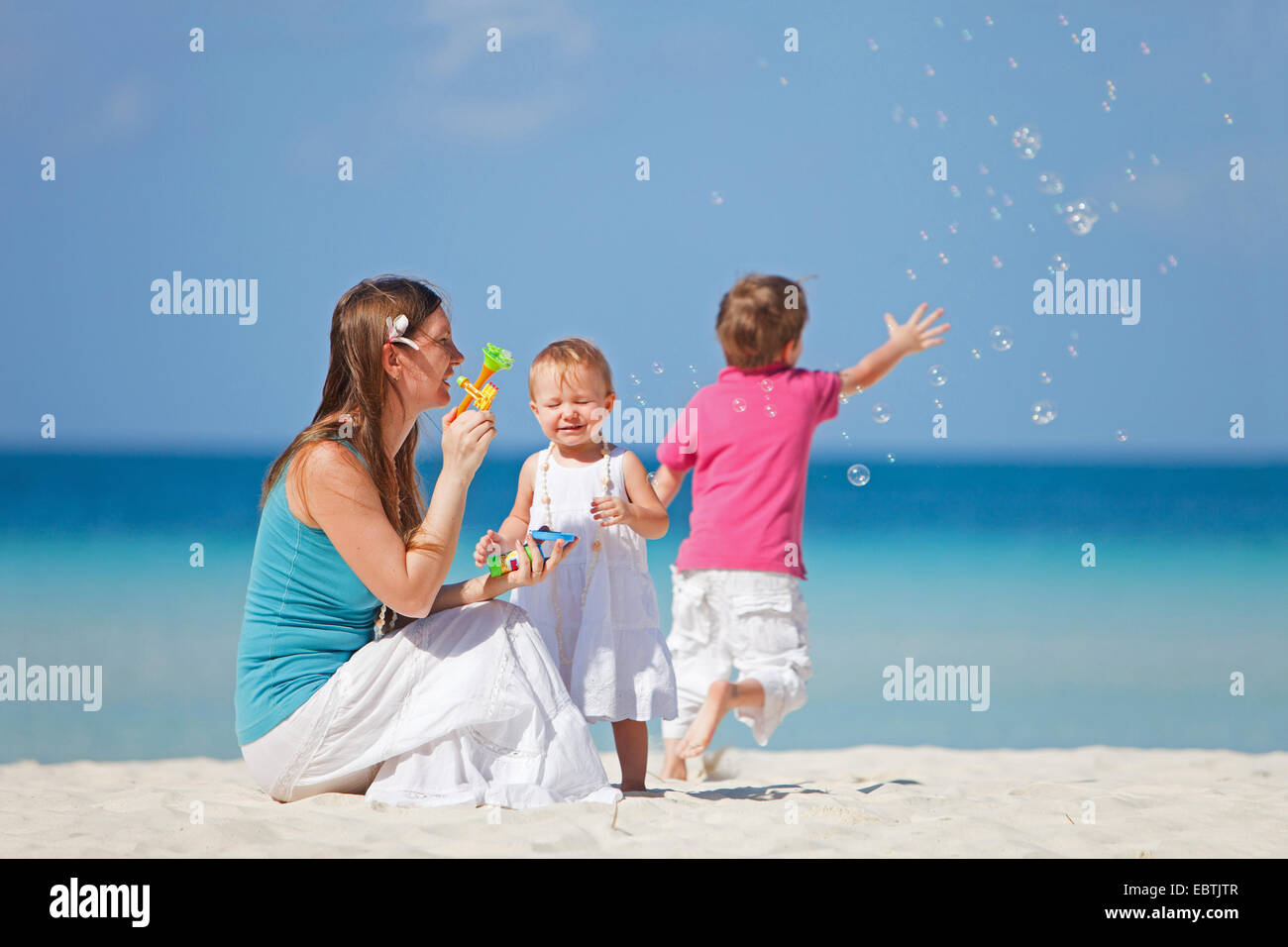 mother sitting with her two children on the beach and blowing bubbles Stock Photo