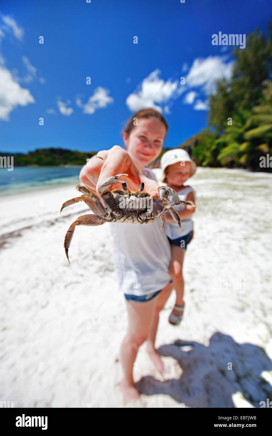 young mother with little child on tropical beach holding a crab to the camera - Stock Image