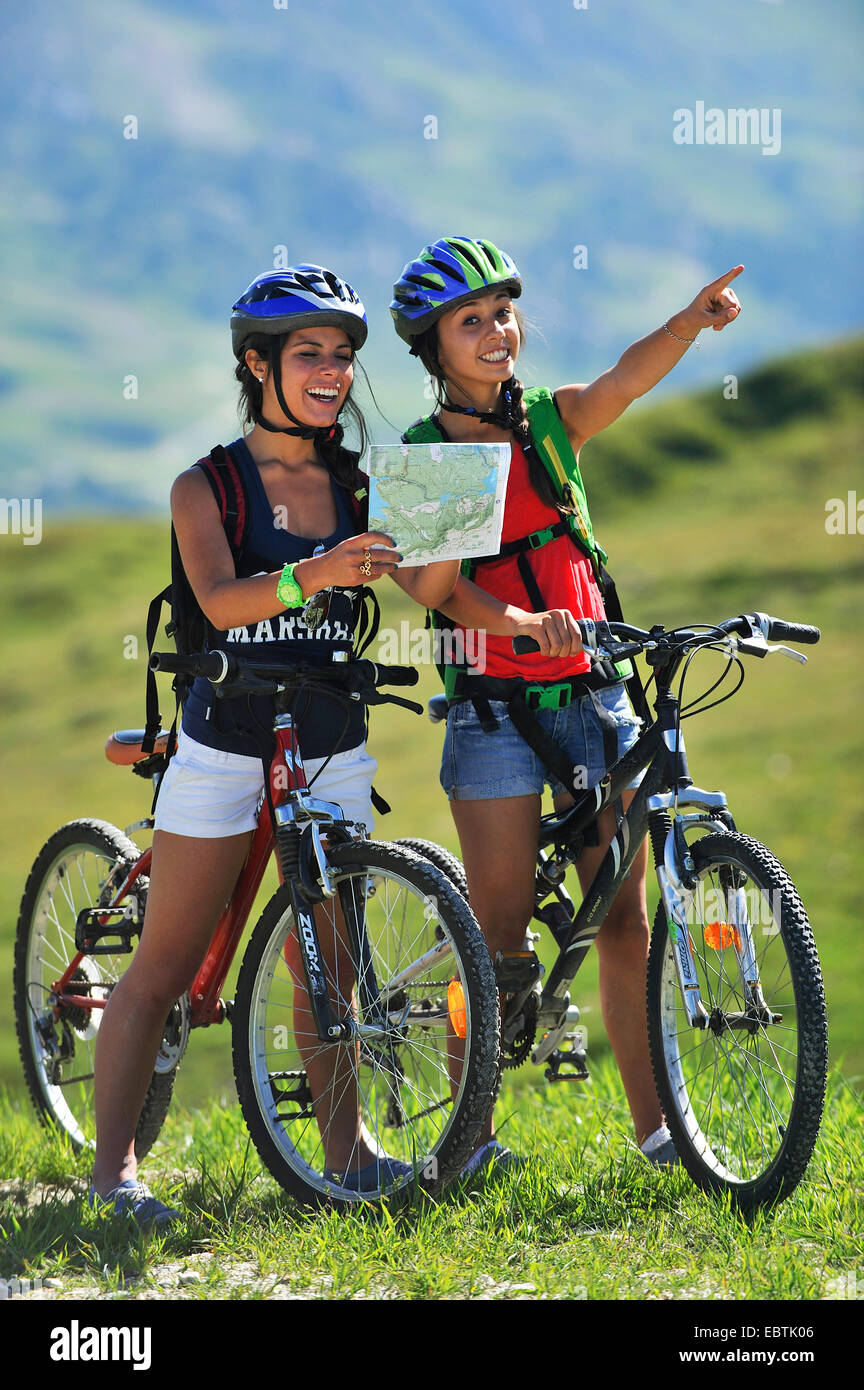 two teenage girls with mountain bikes looking for the right way, France, Savoie Stock Photo