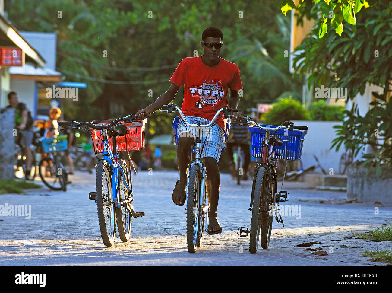 young man cycling and transporting in every hand another bike, Seychelles - Stock Image