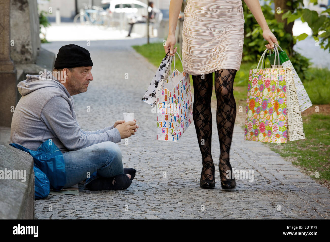 unemployed beggars living on the street, rich young woman with shopping bags passing ihn, Germany - Stock Image