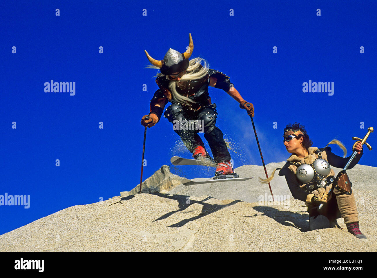 freeride skier disguised as viking going downhill on gravel slope - Stock Image