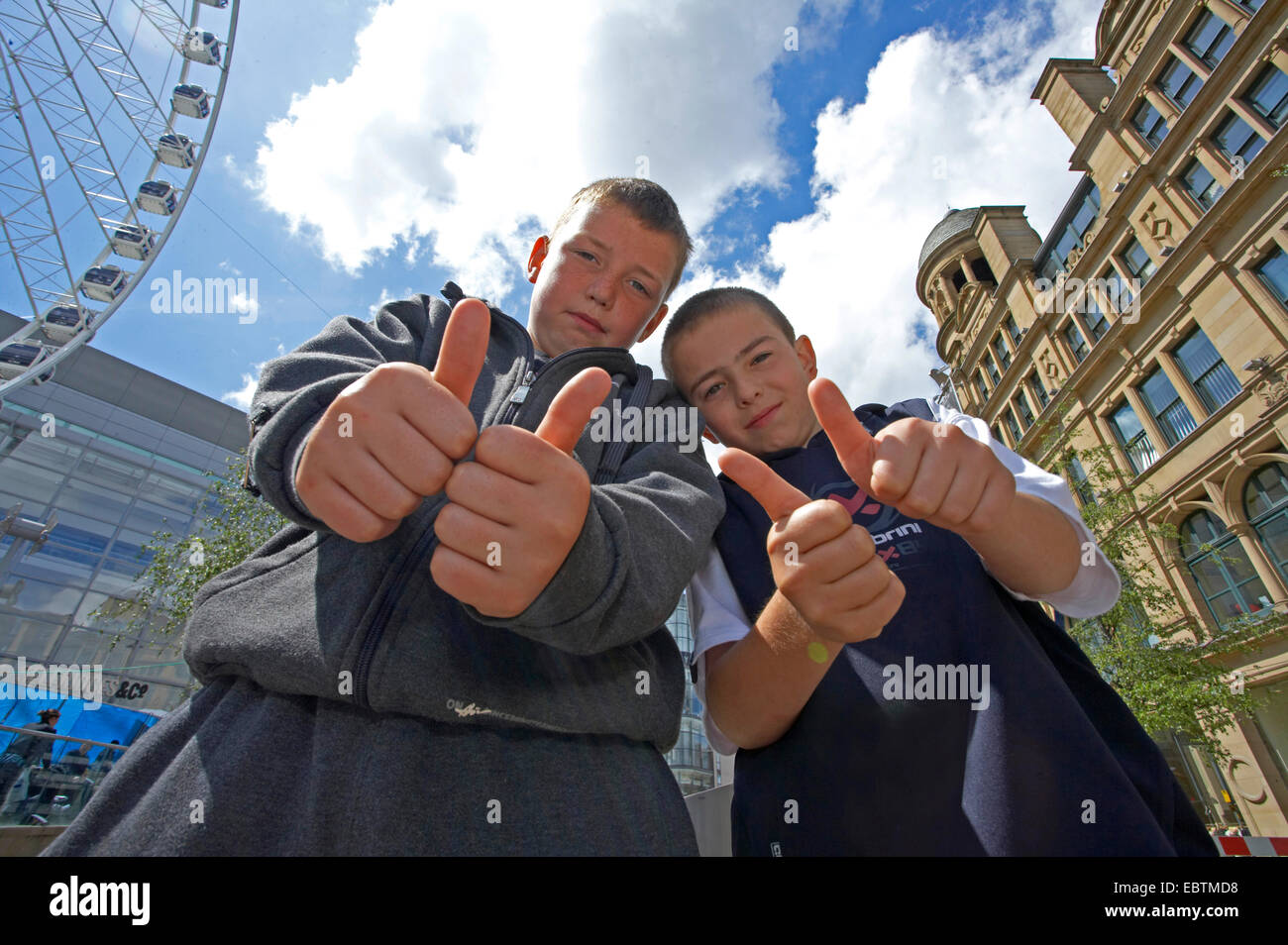 two young boys in the city centre raising their thumbs, United Kingdom, England, Manchester - Stock Image
