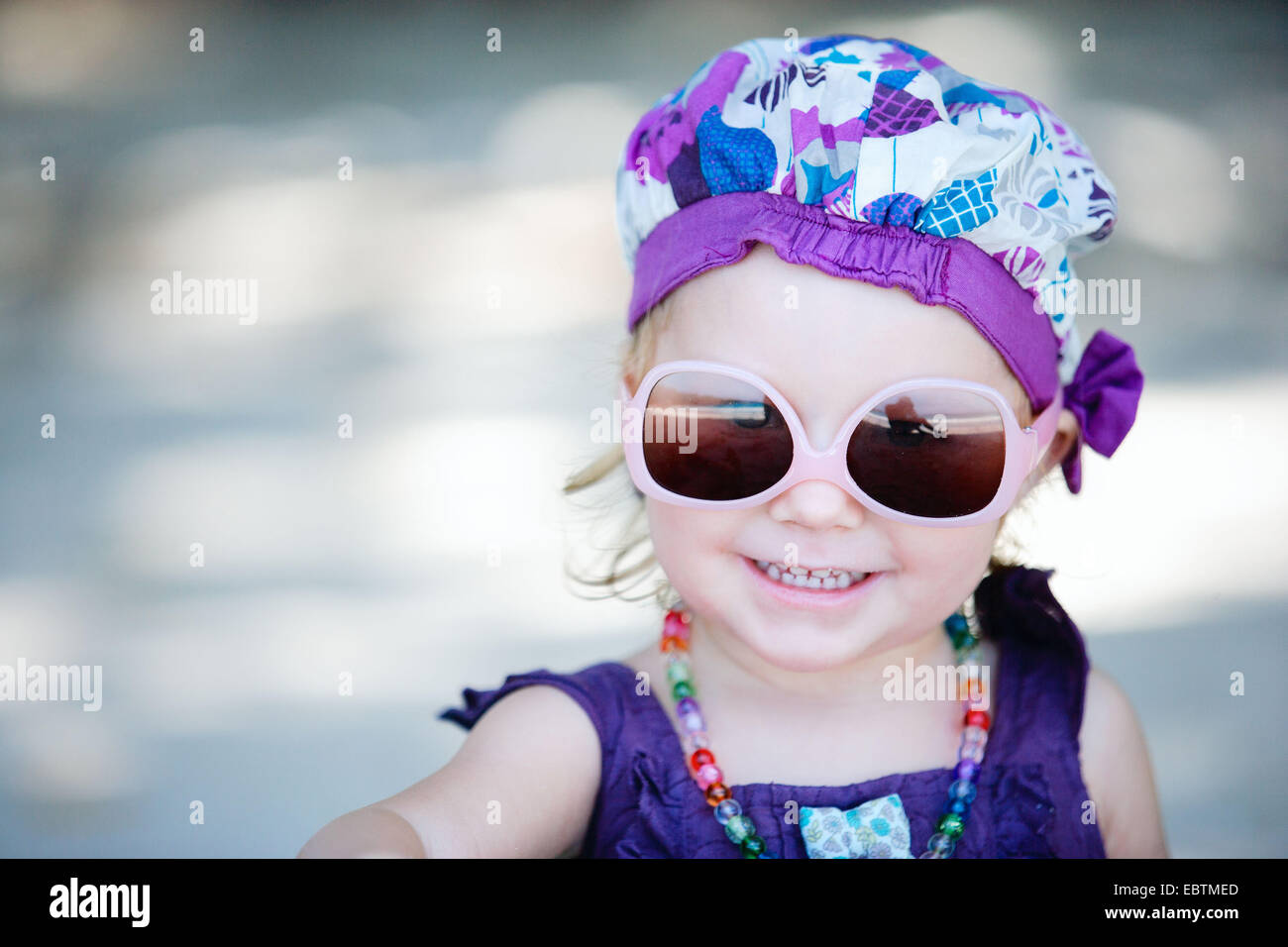 portrait of a little girl wearing sunglasses and fancy clothes Stock Photo