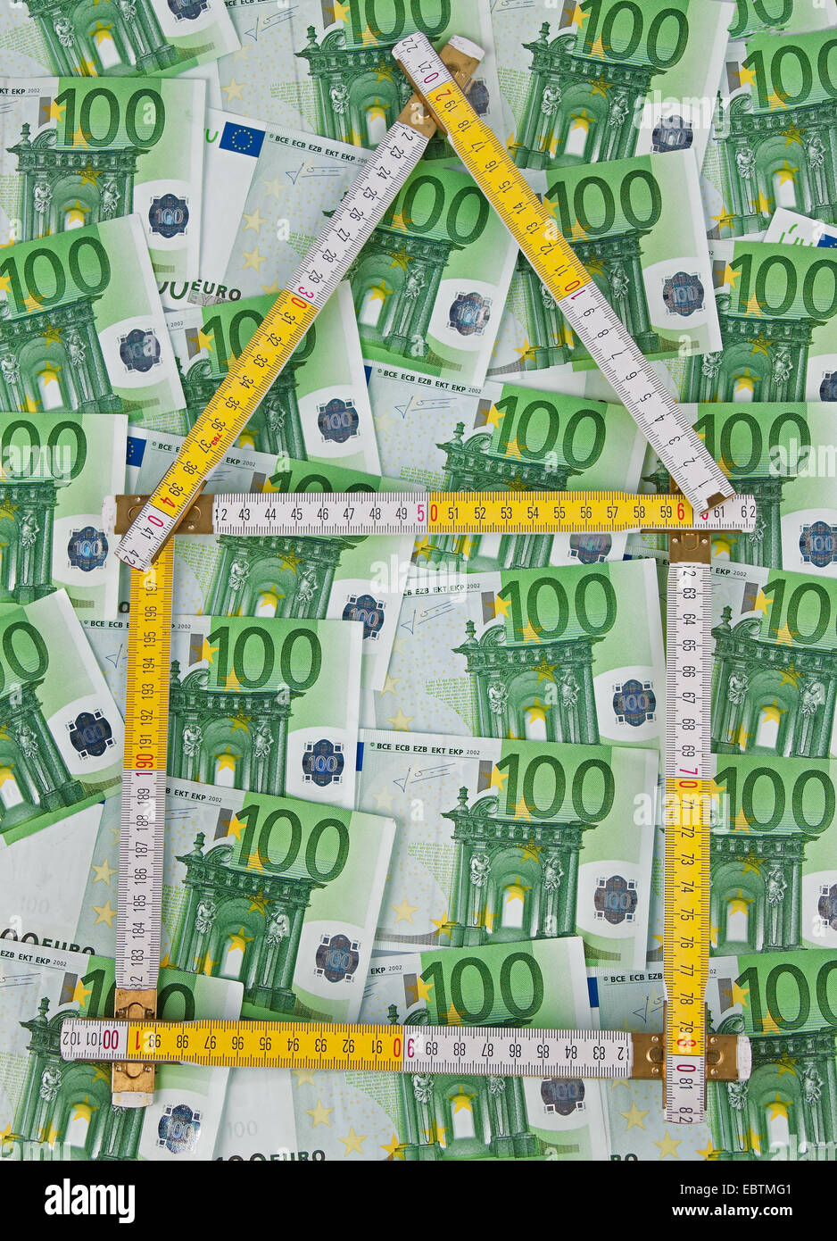 Buying a house. Many euro notes and yardstick, Germany - Stock Image