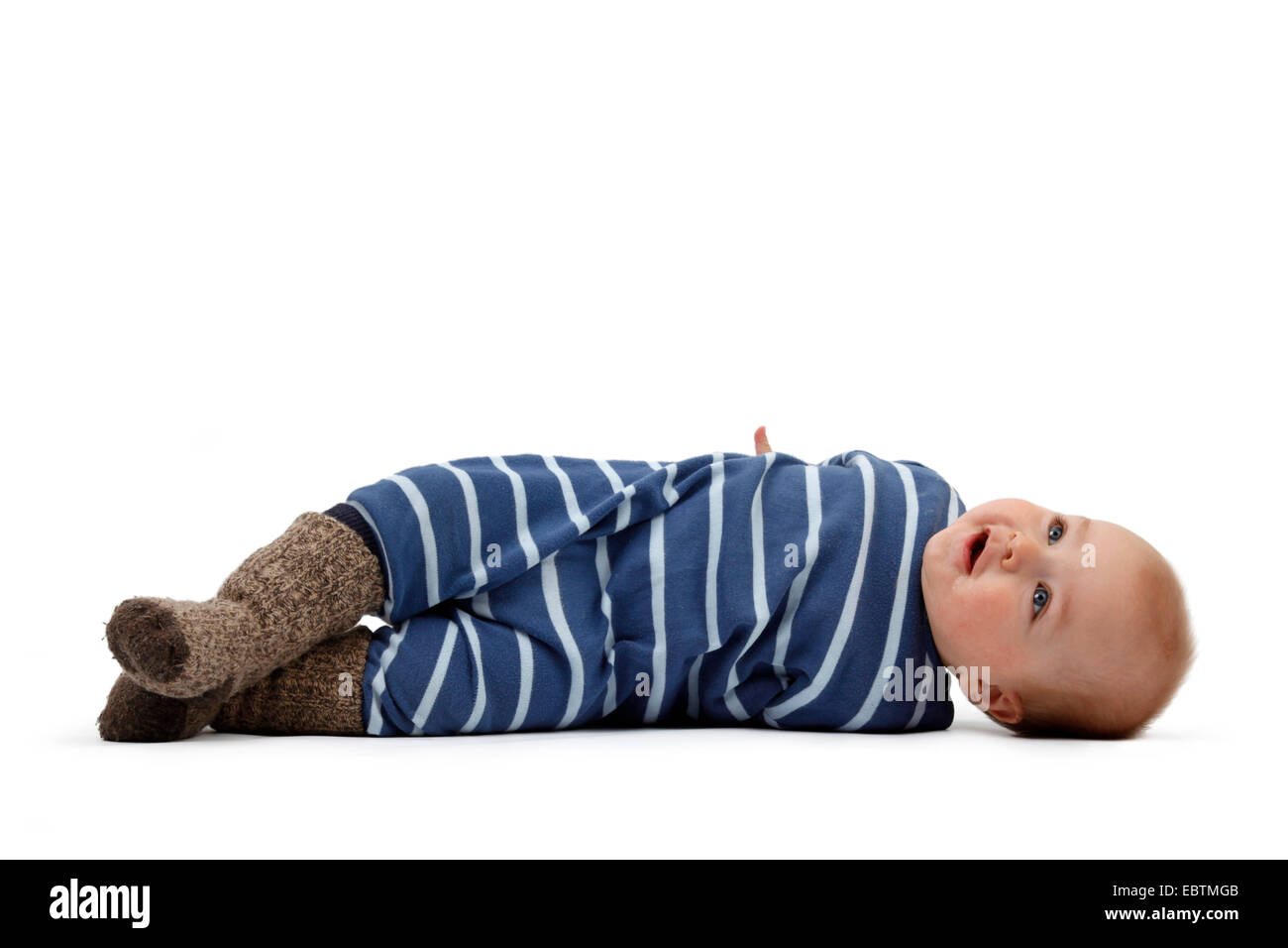 little boy in romper lying on the ground and turning around - Stock Image