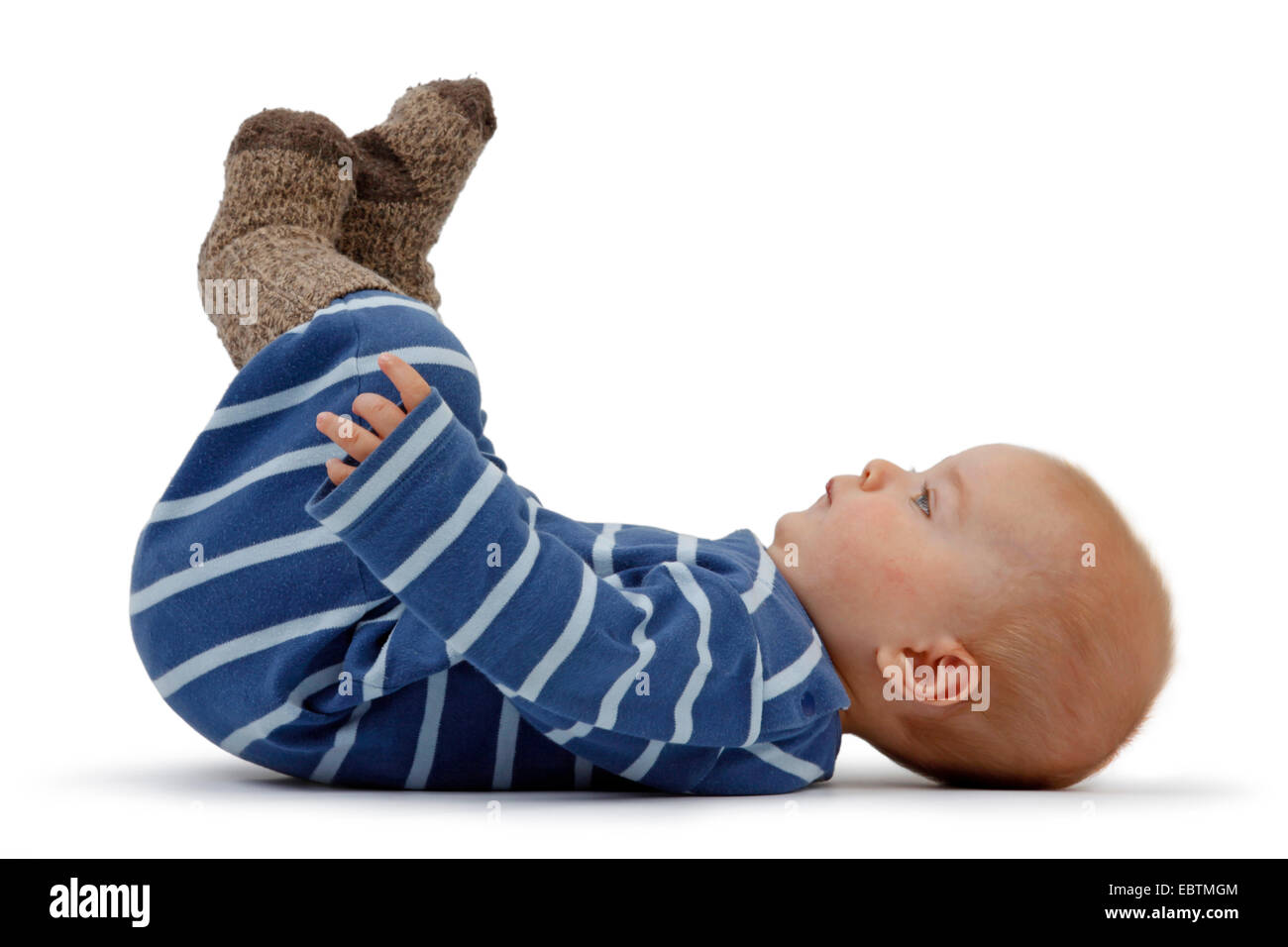 little boy in romper lying at the back and tucking up legs - Stock Image