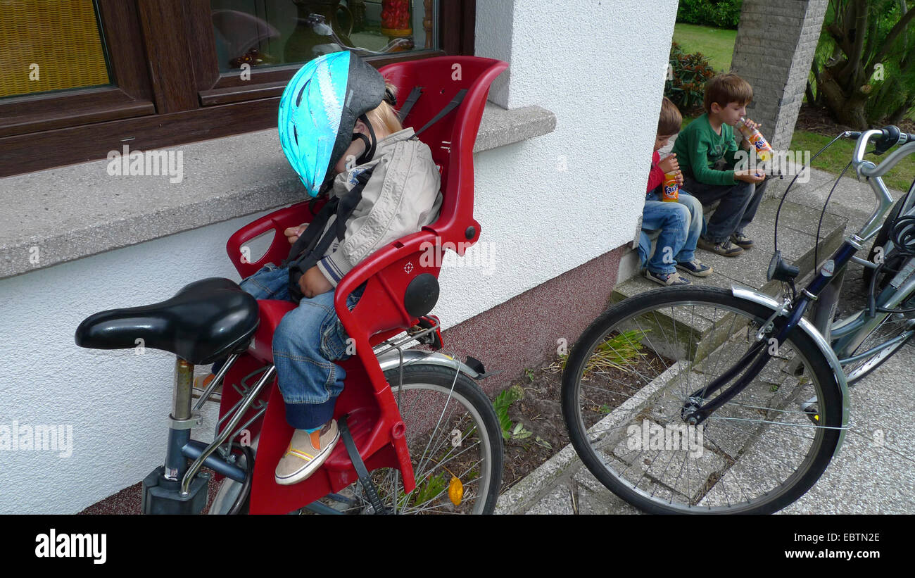 three little boys having returned from a bicycle tour: two drinking, one sleeping in the child seat on a bike - Stock Image