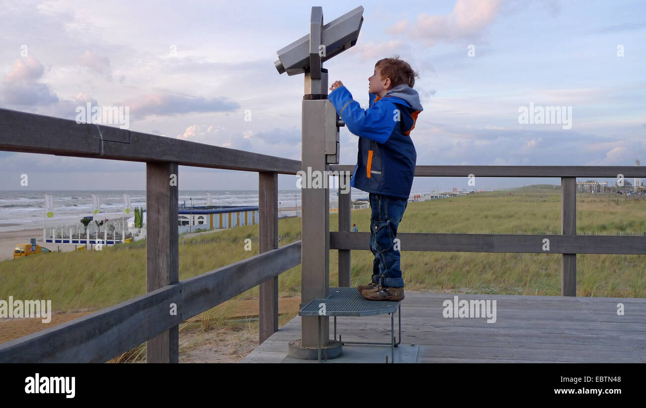 little boy with coin telescope at the North Sea, Netherlands - Stock Image