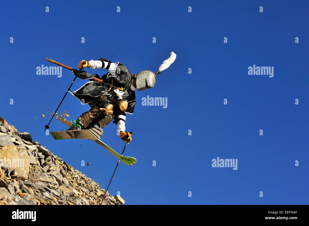 freeride skier disguised as knight going downhill on gravel slope - Stock Image