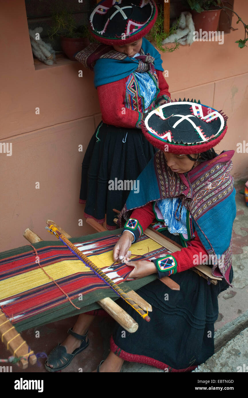 young woman in traditional dress working at a weaving loom at the local artisan workshop, Peru, Chincheros Stock Photo