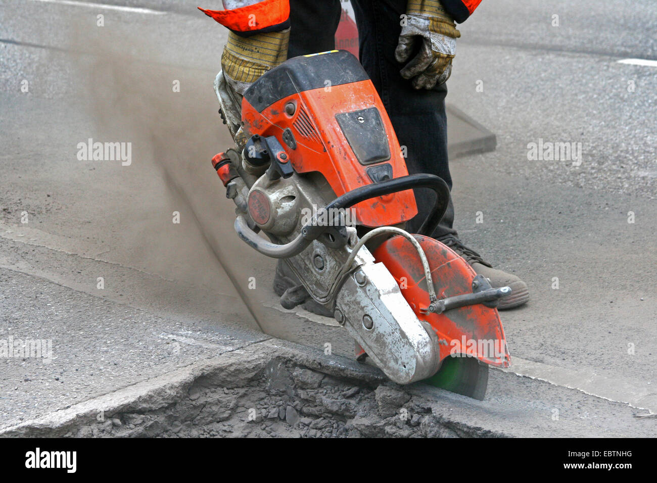 cutting the old road surface with angle grinder, Germany, North Rhine-Westphalia - Stock Image