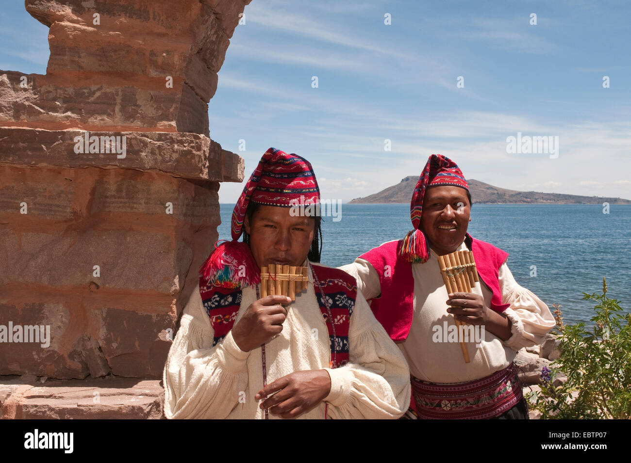 two Indians in traditional clothes playing panflutes at the shore of Lake Titicaca, Peru, Taquile Island, Lake Titicaca - Stock Image