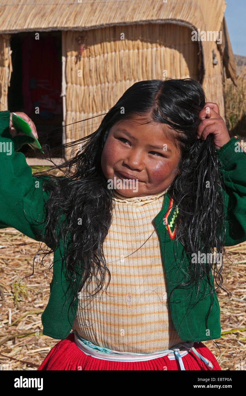 Quechua or Uros Indian girl on one of 42 floating islands on Lake Titicaca called 'Uros Islands', self-built - Stock Image