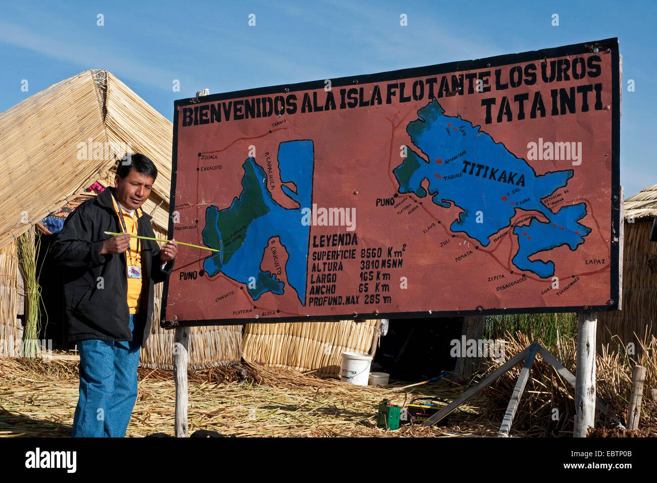Tourist at an information sign on one of 42 floating islands on Lake Titicaca called 'Uros Islands', self - Stock Image
