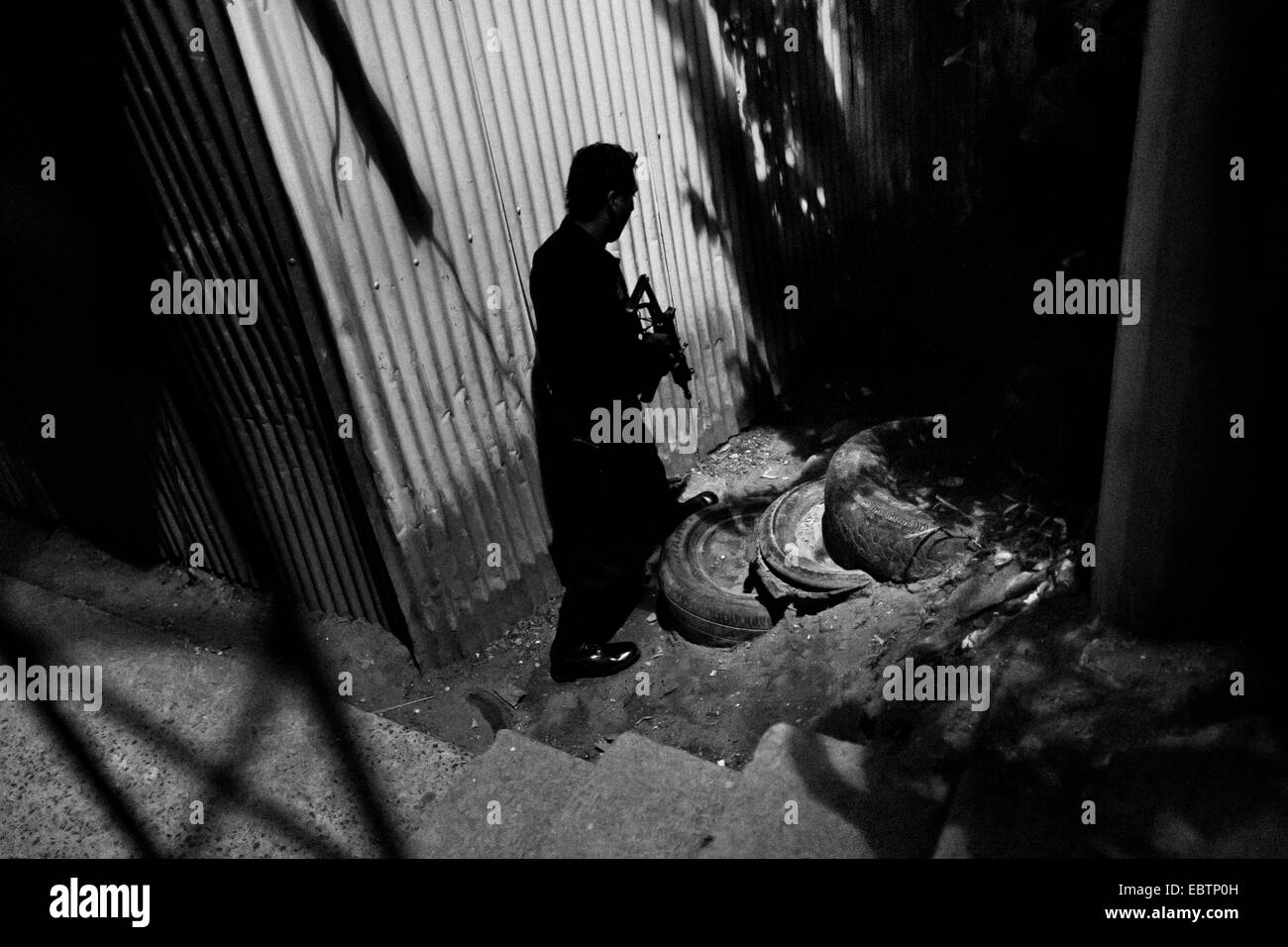A policeman from the special emergency unit (Halcones) chases supposed gang members during the night in a gang neighbourhood of San Salvador, El Salvador, 15 December 2013. Stock Photo