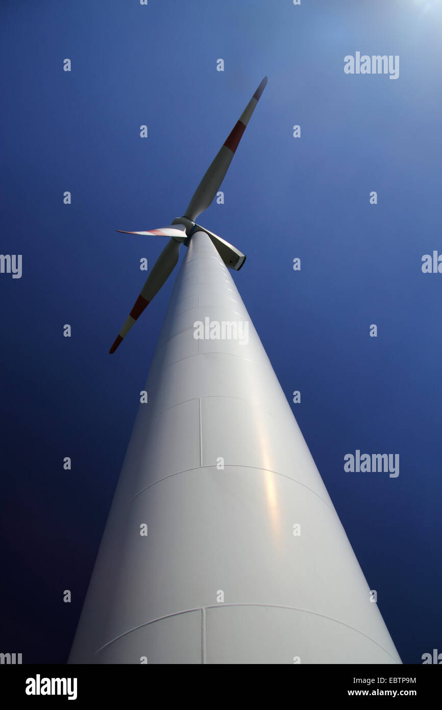 view up a wind power plant looming into a clear blue sky - Stock Image