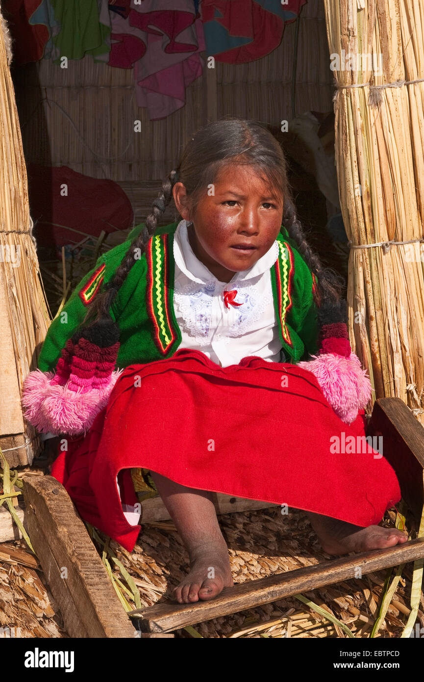 Uro girl sitting in the entrance of a hut on the floating Uros Islands, Peru, Lake Titicaca - Stock Image