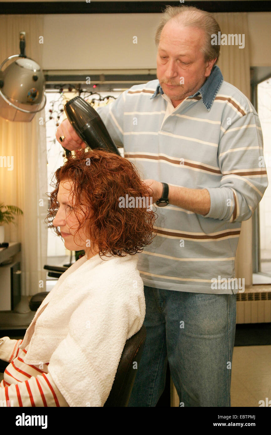 hairdresser drying woman's hair - Stock Image